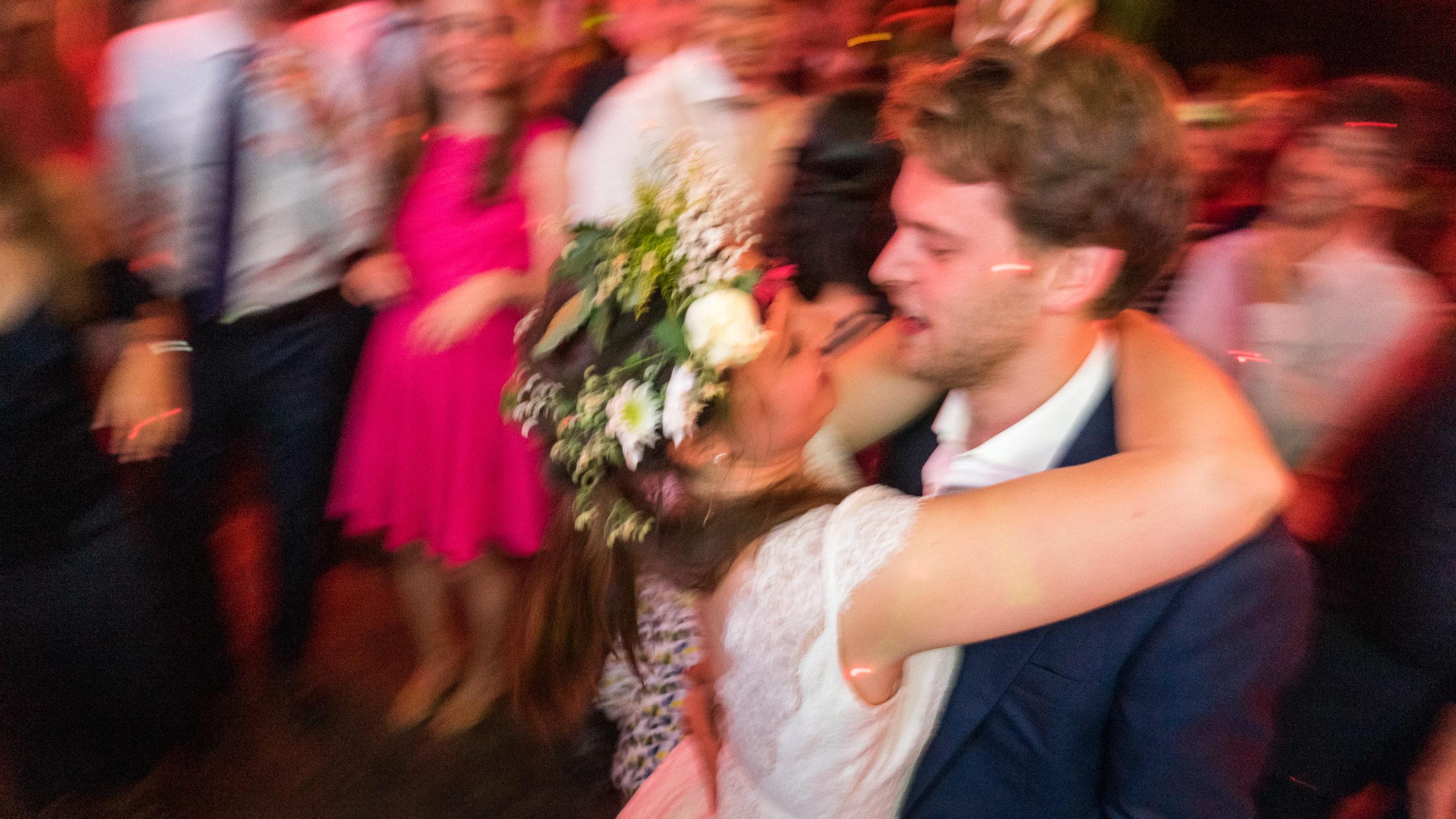 Photographie de mariage à Montpellier. Les deux mariés enlacés dans une dance au milieu de leurs invités, à la nuit tombée. Photographe studio sud