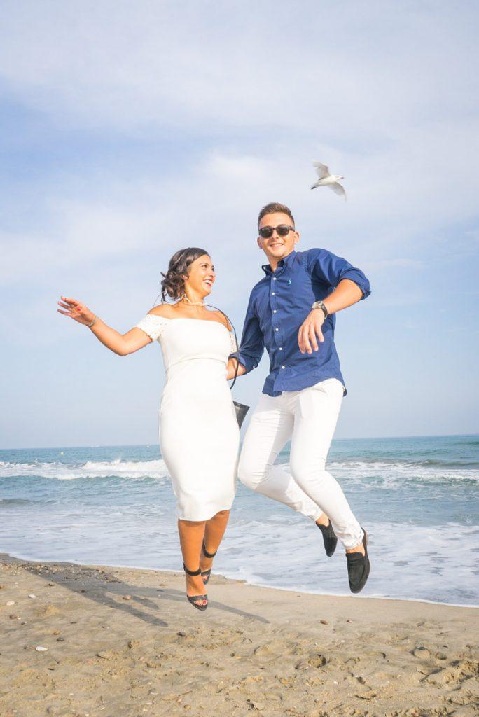 Un couple d'invité au mariage saute sur la plage de Sète