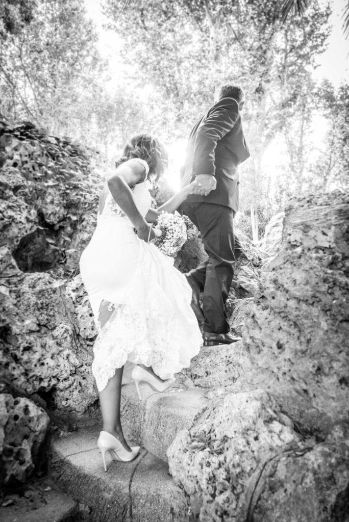 Le marié prend la main de la mariée et l'emmène en haut de marches abruptes.