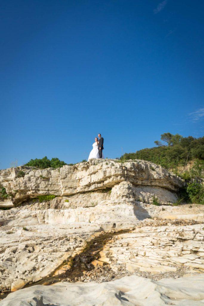 Dans les gorges du Sautadet, un couple de marié apparait en haut d'une falaise, petit, mais au centre de la pierre et de la garrigue.