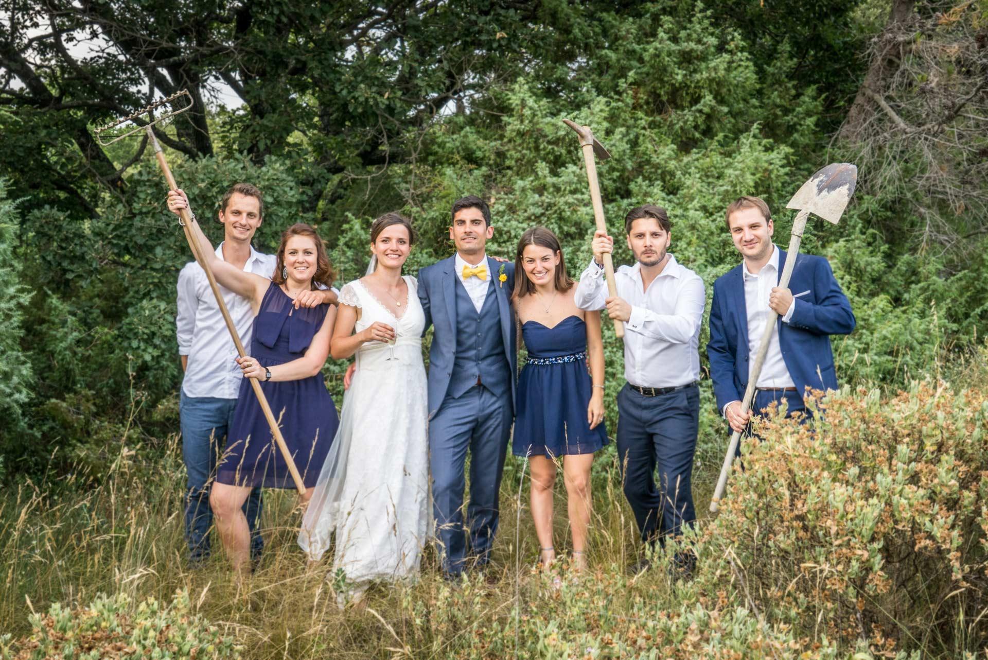 Mariage à Uzes. Les mariés posent avec leurs amis dans un champ. Ils brandissent des outils de travailleurs.