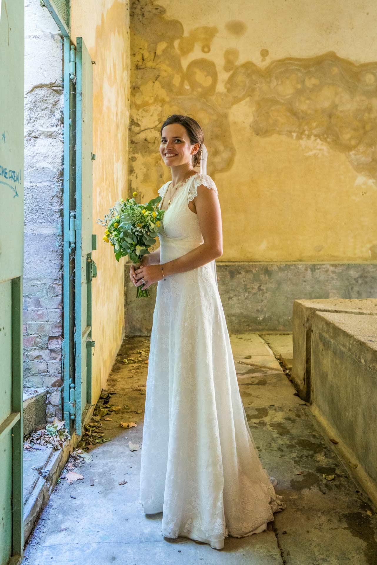 La mariée dans un ancien lavoire, tenant son bouquet.