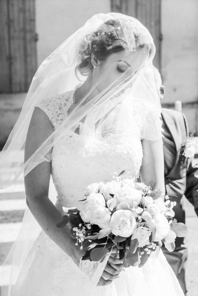 la mariée voilée regarde son bouquet de fleurs blanches avant d'entrer dans l'église