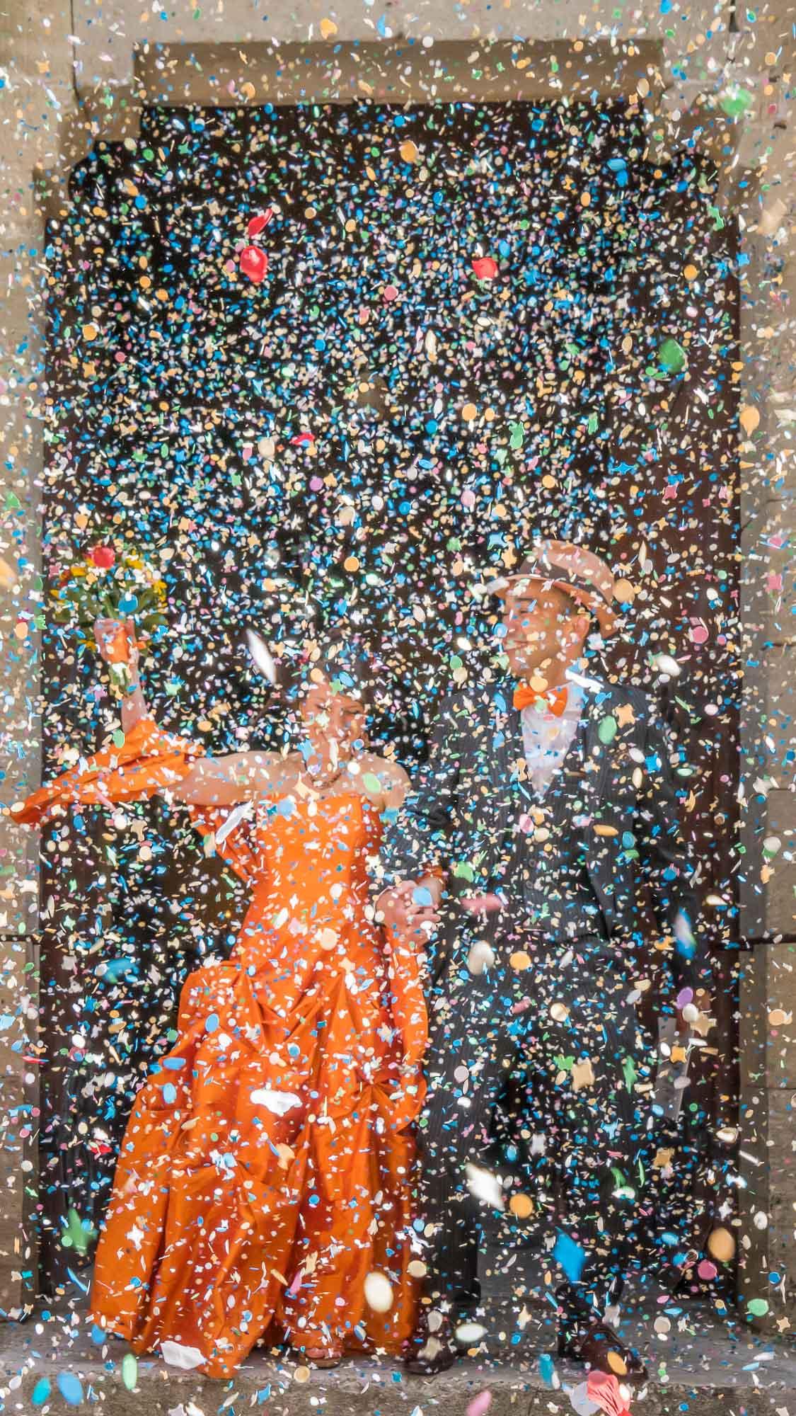 les mariés sortent de l'église sous une pluie dense et multicolore de confettis
