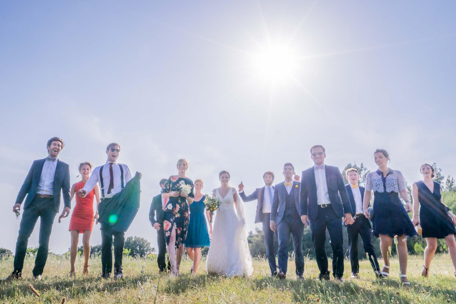 les mariés et leirs invités marchent dans un champ sous le soleil