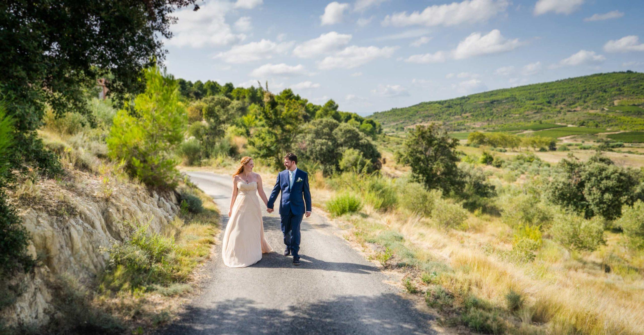 Photographie de Mariage. Les deux mariés marchent sur une route de garrigue main dans la main en se regardant amoureusement. Nîmes, Gard.