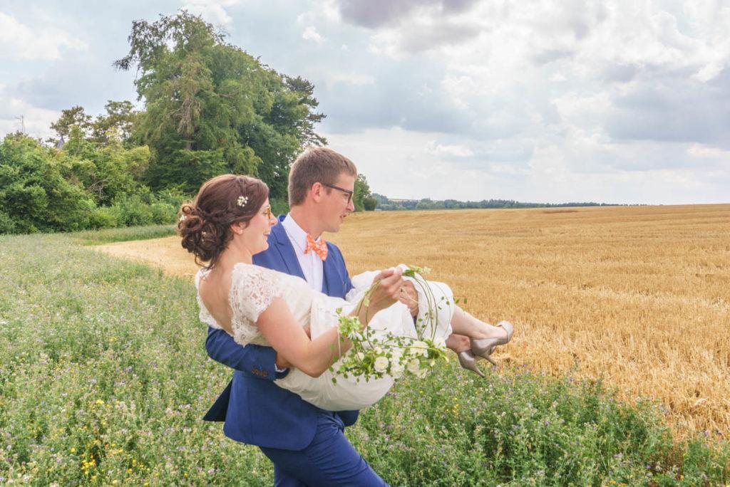 le marié porte la mariée dans un champ