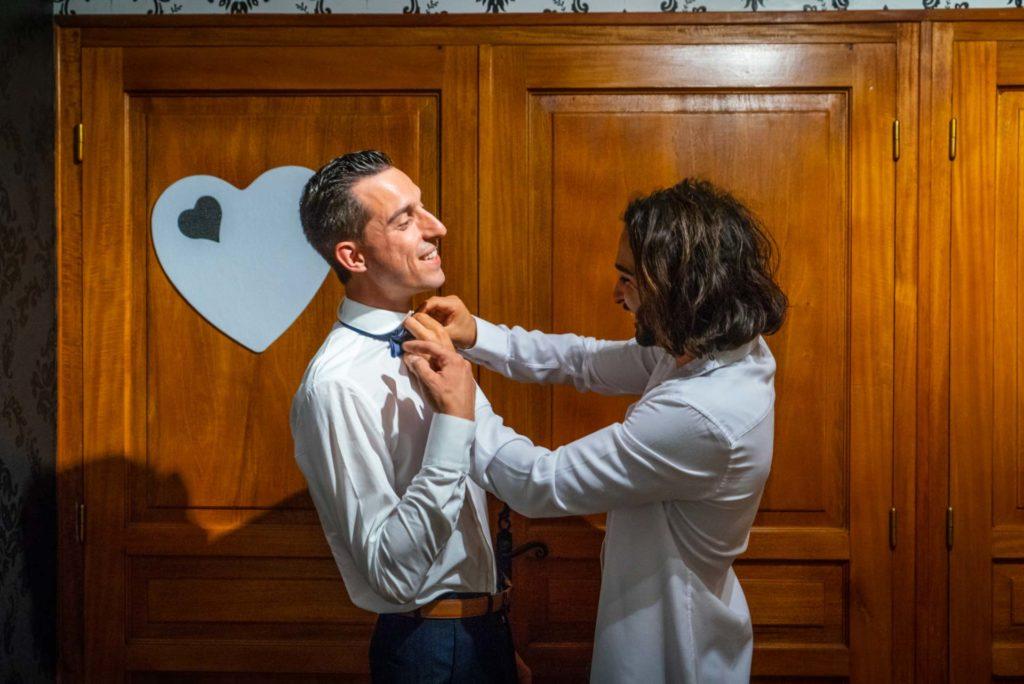 une garcçon d'honneur fixe le nœud papillon du marié