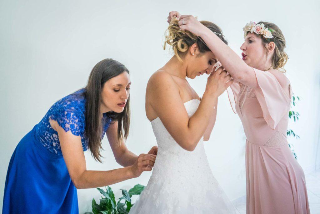 les demoiselles d'honneur aident la mariée à s'habiller