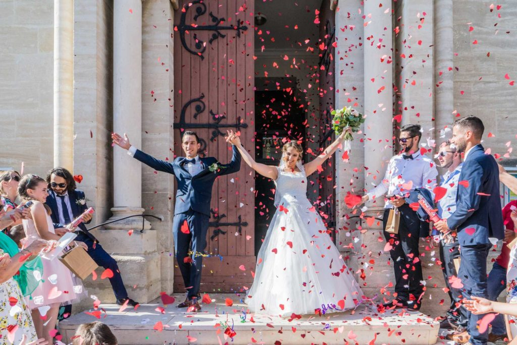 les mariés sortent triomphalement de l'église, levant les bras sous une pluie de confettis rouges en forme de coeur