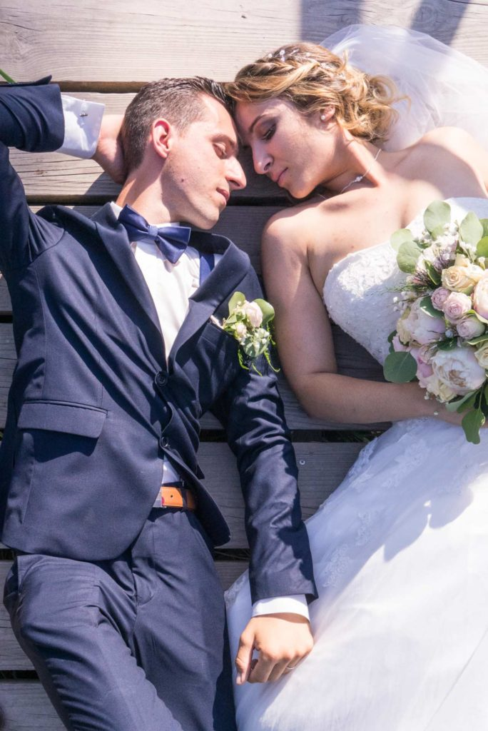 Les mariés allongés, tête contre tête, rêvent les yeux fermés.