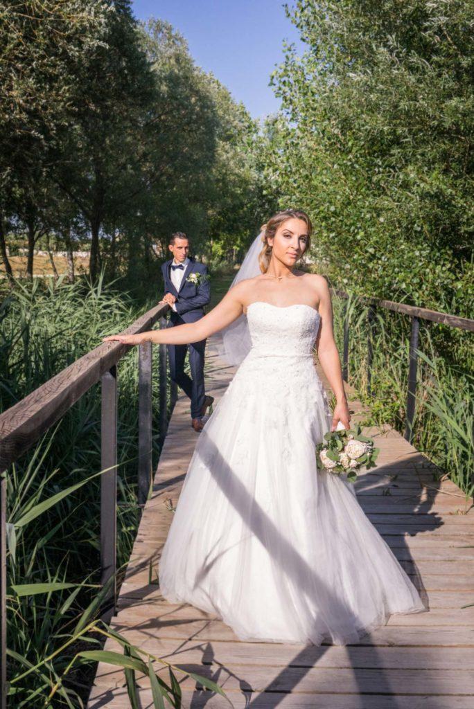 Les mariés posent sur un pont de bois traversant une forêt de roseaux.