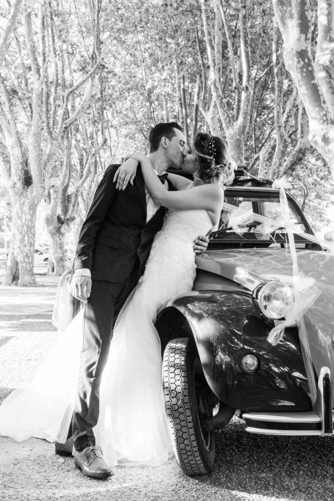 les deux mariés s'embrassent contre une voiture deux chevaux décorée pour le mariage