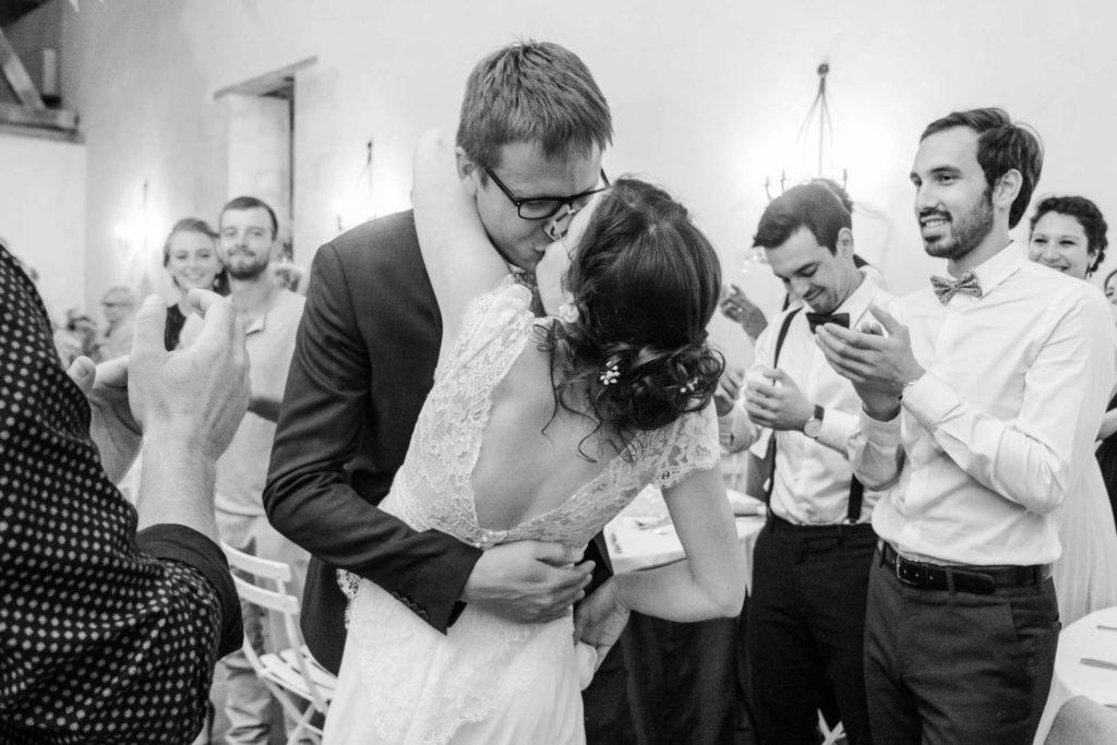 les mariés s'embrassent passionnément au milieu de leurs invités qui applaudissent