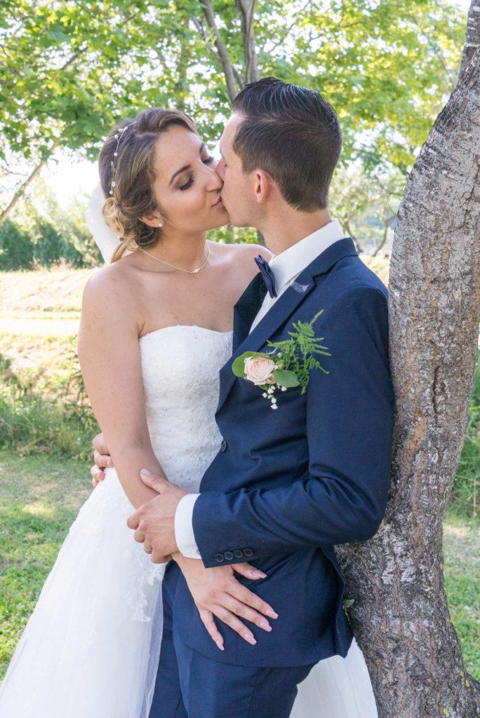 les mariés s'embrassent contre un arbre