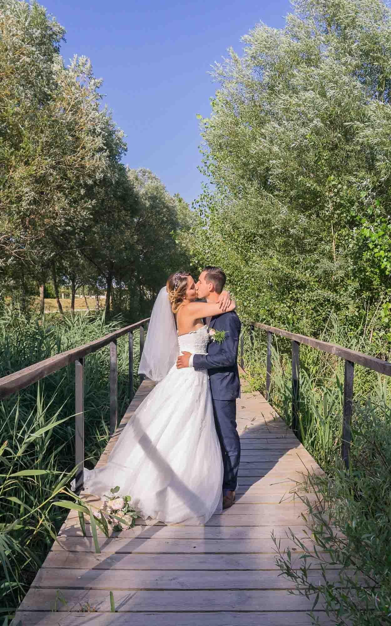 Les mariés s'embrassent sur un pont traversant une rivière de roseaux.