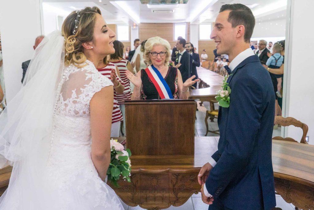les deux mariés se regardent devant la maire qui tend les bras, les déclarant mari et femme